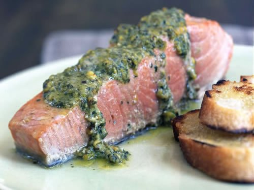 A fillet of troll caught cocho salmon from Alaska on dish with sauce.